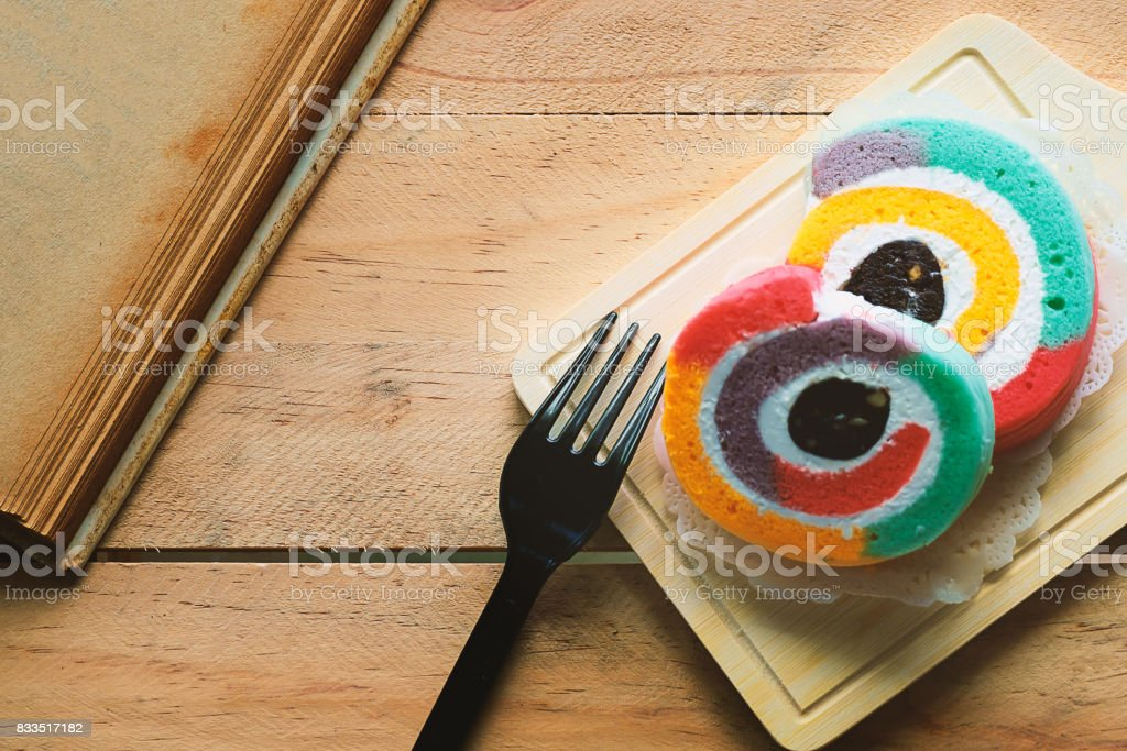 Rainbow color of yam roll, bakery with a book on the wooden table stock photo