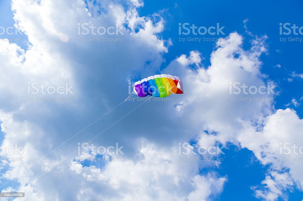 rainbow colored child's kite on blue sky with clouds stock photo