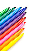 Rainbow colored markers on white background