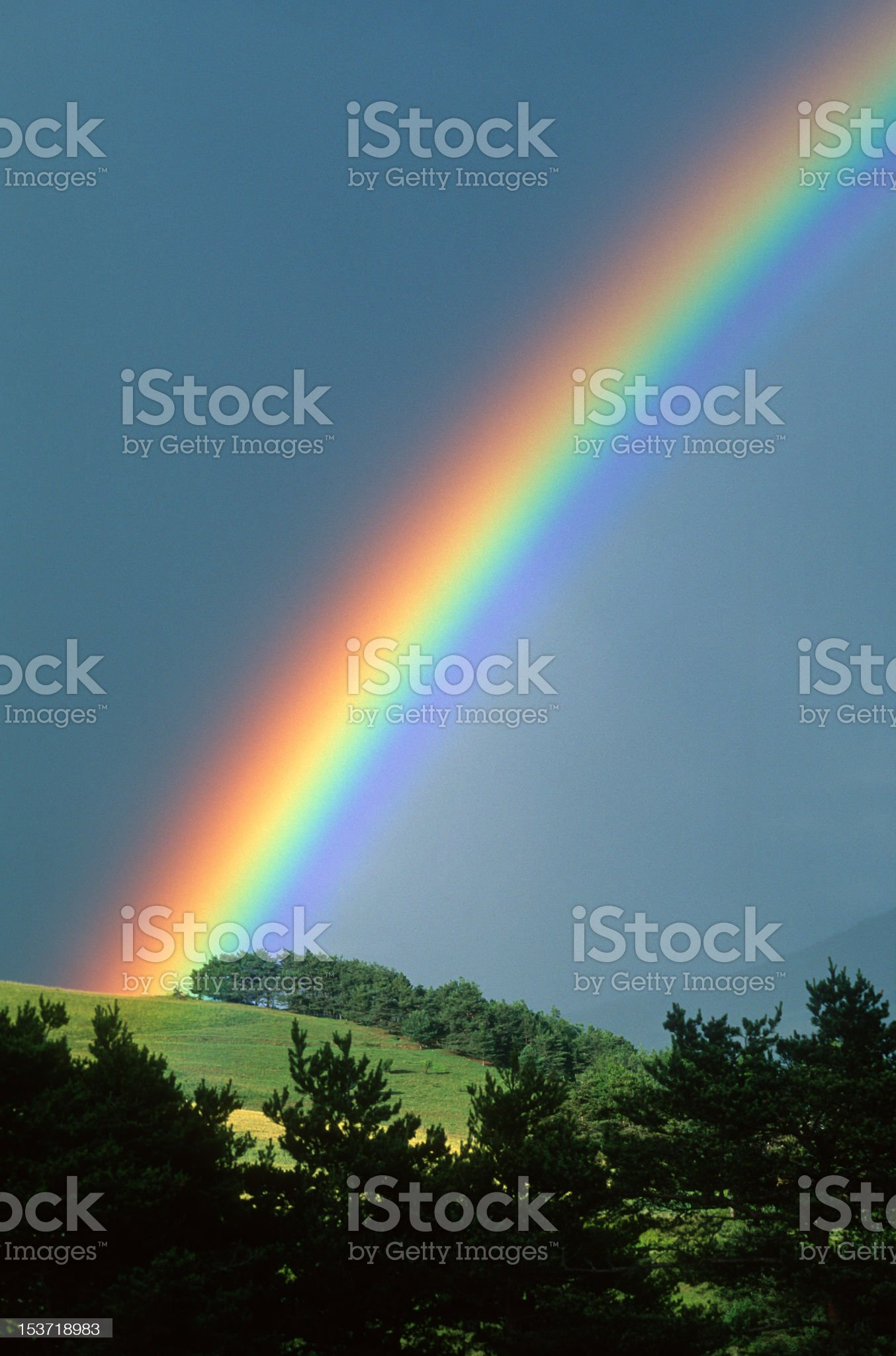Rainbow coming up over a hillside royalty-free stock photo