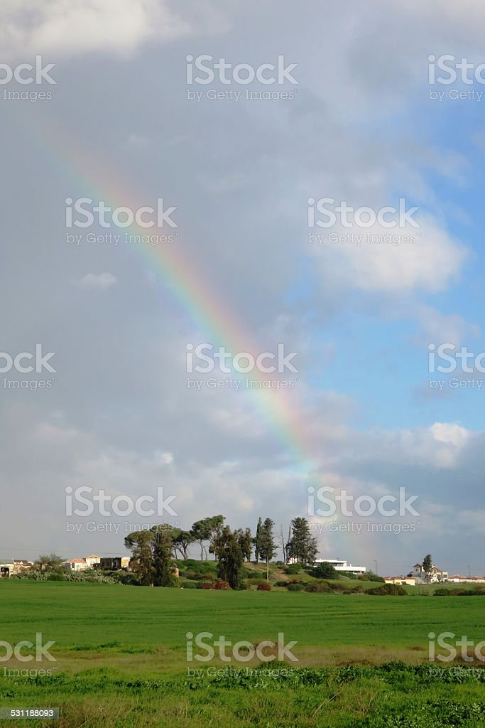 Rainbow coming up over a hillside stock photo