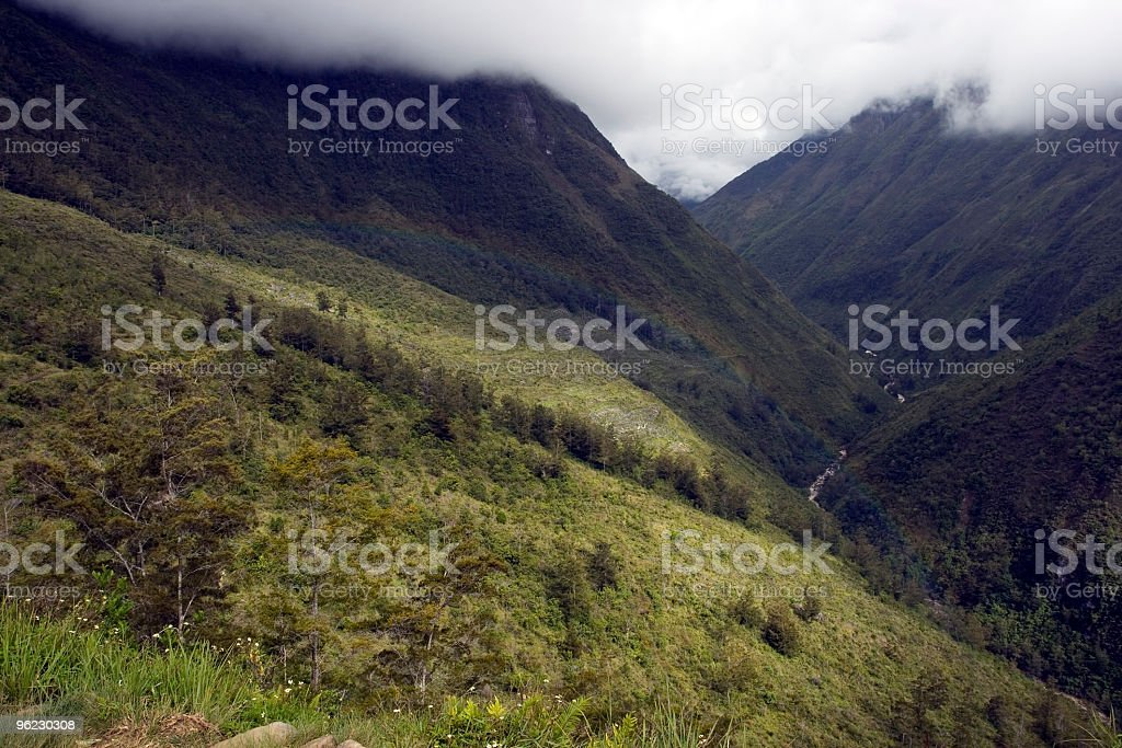 Rainbow emerging in New Guinea valley stock photo