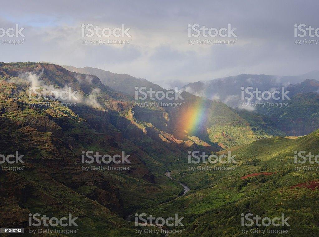 Rainbow falling on river in Waimea Canyon stock photo