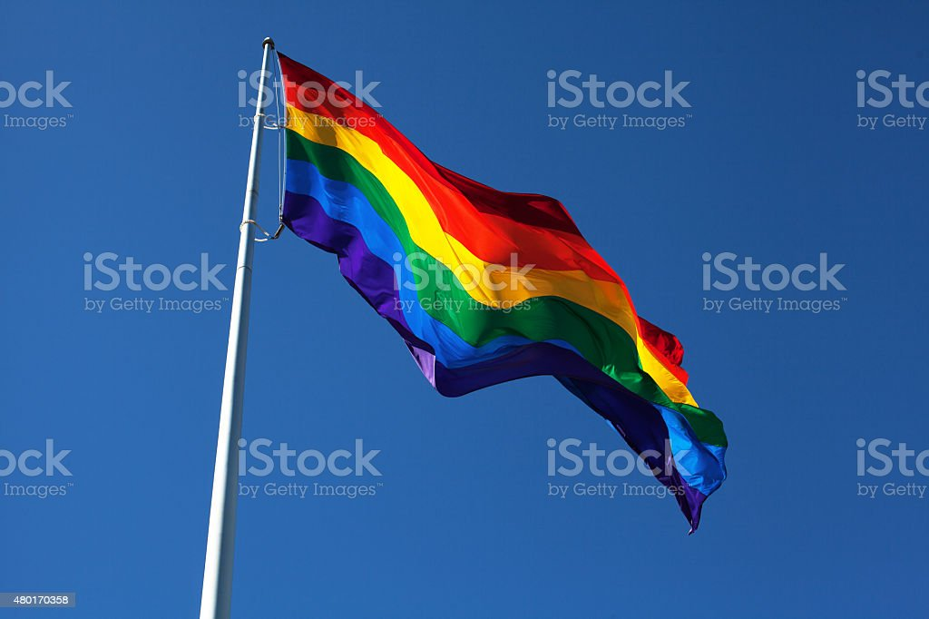 Rainbow flag fluttering in the sky stock photo