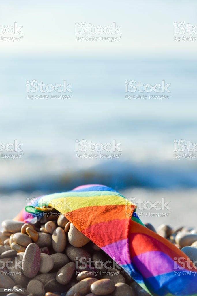 rainbow flag in a shingle beach stock photo