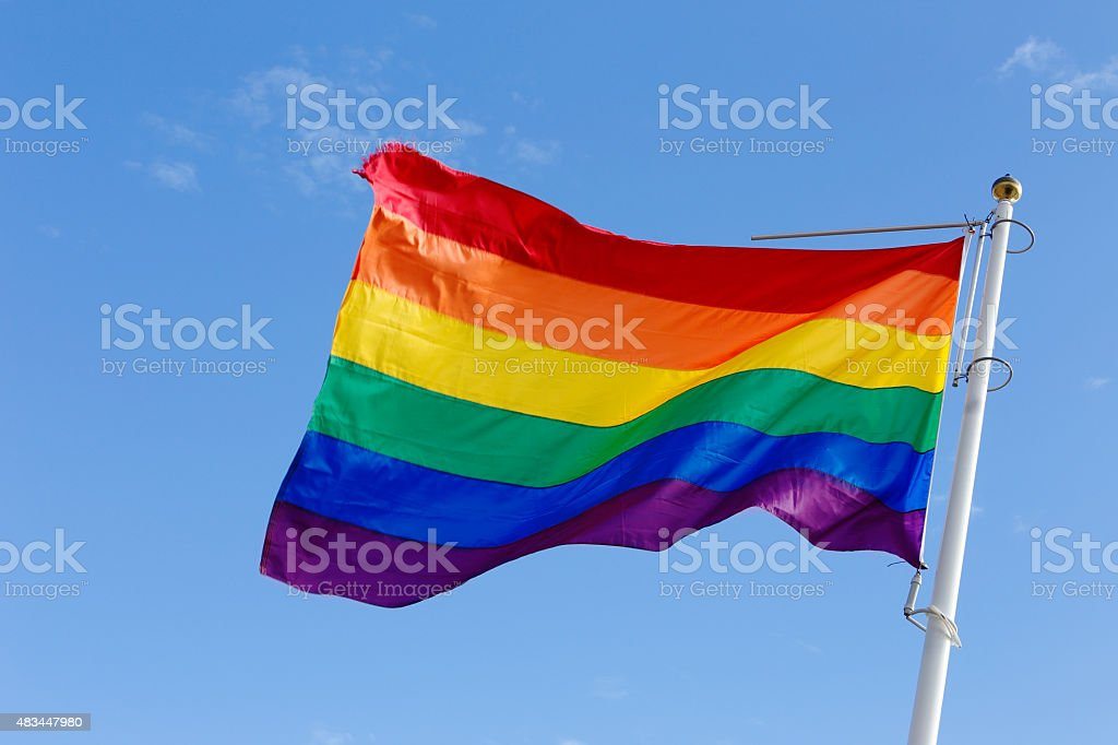 Rainbow flag in the wind stock photo