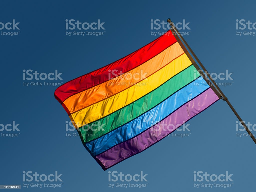 Rainbow Flag of LGBTQ Nation Backlit Against Blue Sky. stock photo
