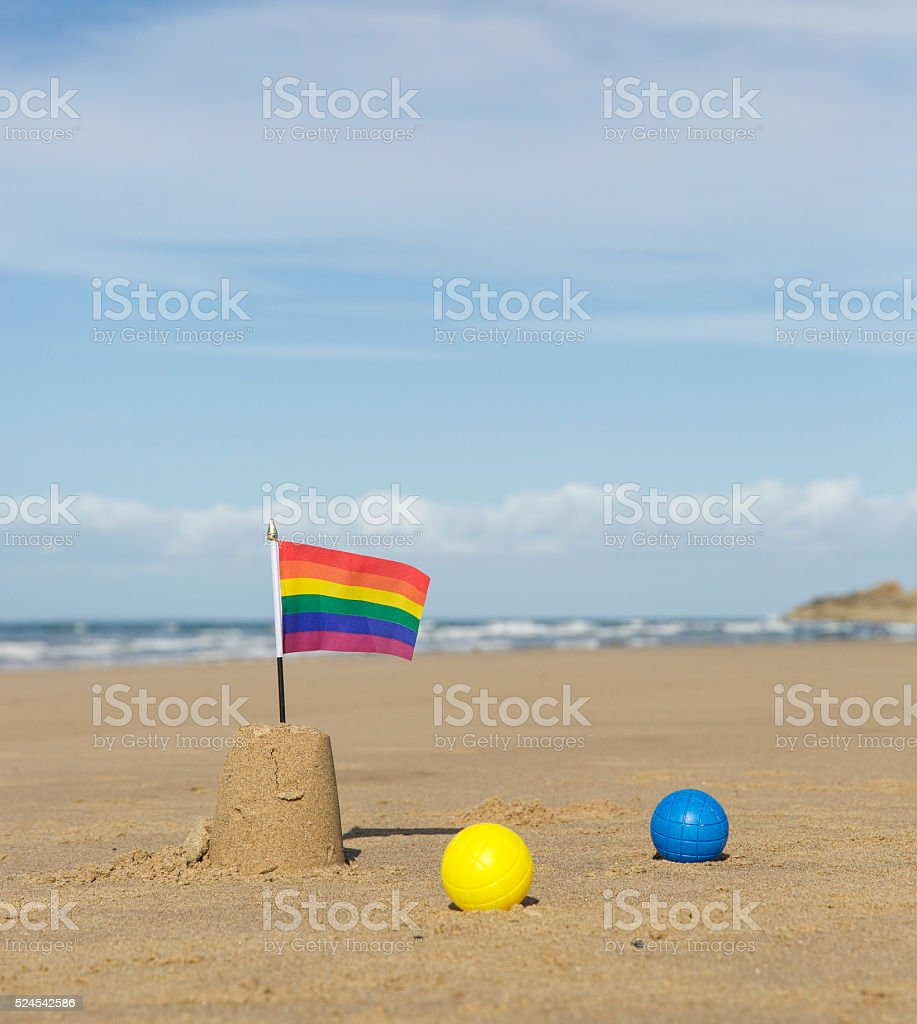 Rainbow flag on a sandcastle surrounded by coloured balls stock photo