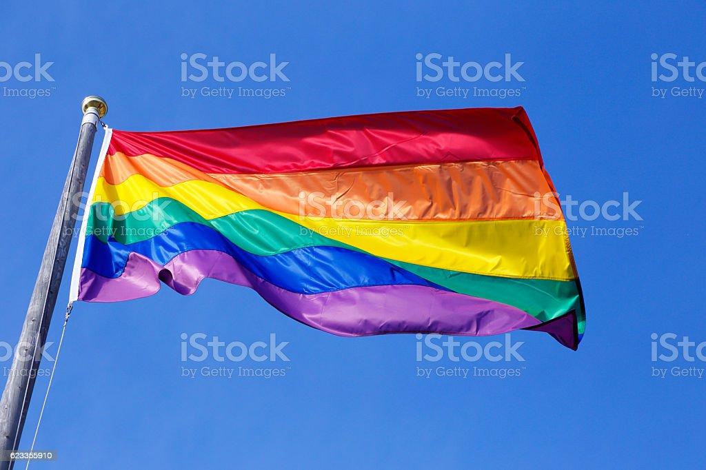 Rainbow flag on blue stock photo
