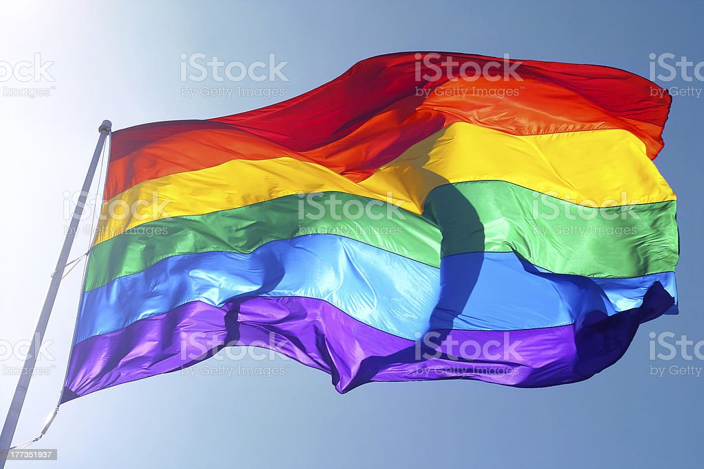 Rainbow flag, sun, wind, and blue sky stock photo