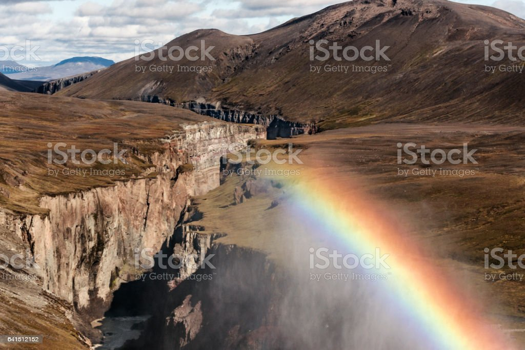 Rainbow in the mist over a rocky canyon stock photo