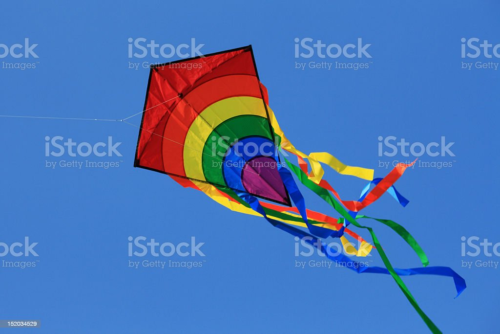 Rainbow kite with multiple tails flying in the cloudless sky stock photo