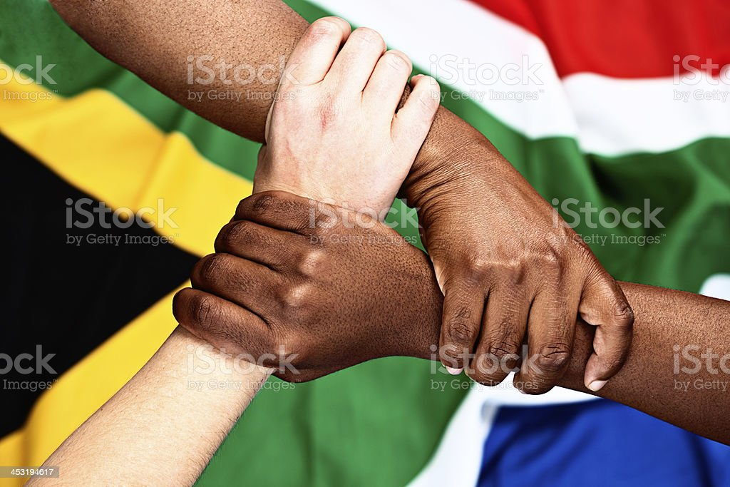 Rainbow nation unity: three clasped hands against South African flag stock photo