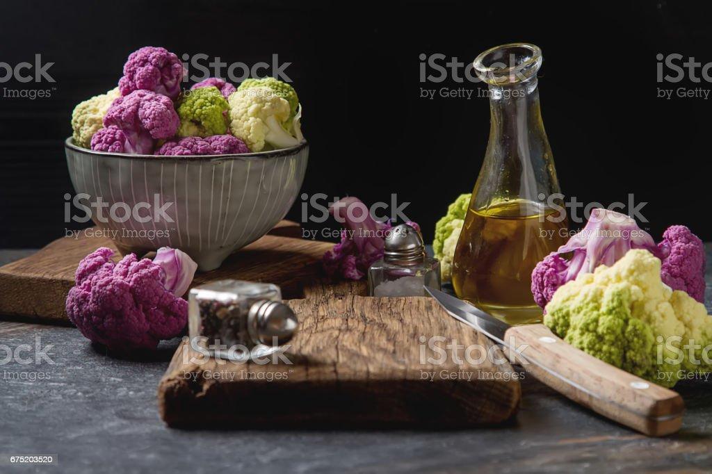 Rainbow of organic cauliflower and Romanesco broccoli on wooden table. stock photo