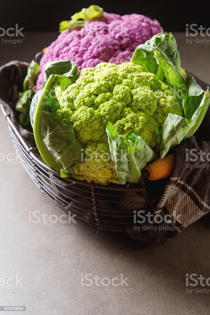 Rainbow of organic cauliflower in a metal basket with a dark cloth. Grey table. stock photo