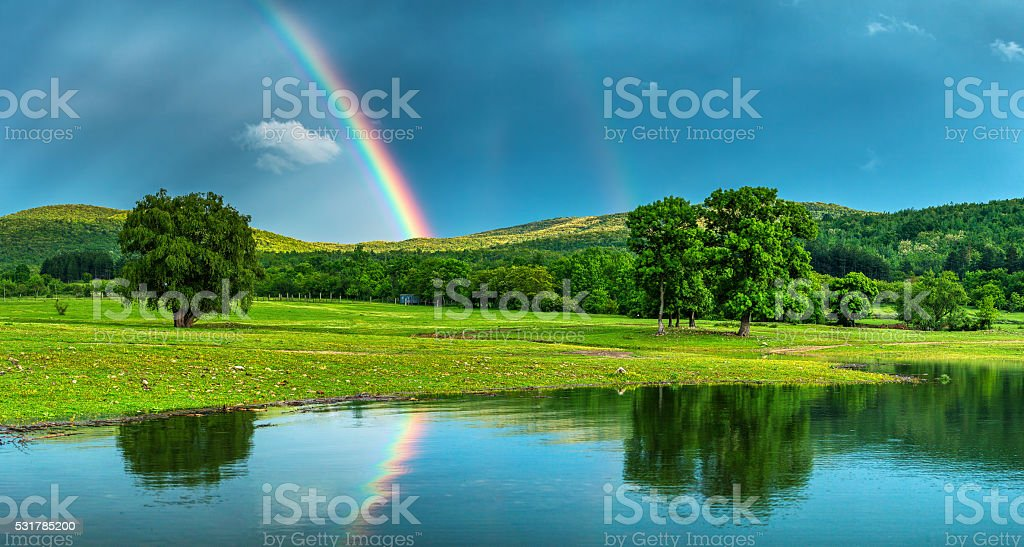 Rainbow over a lake, reflected in the water stock photo