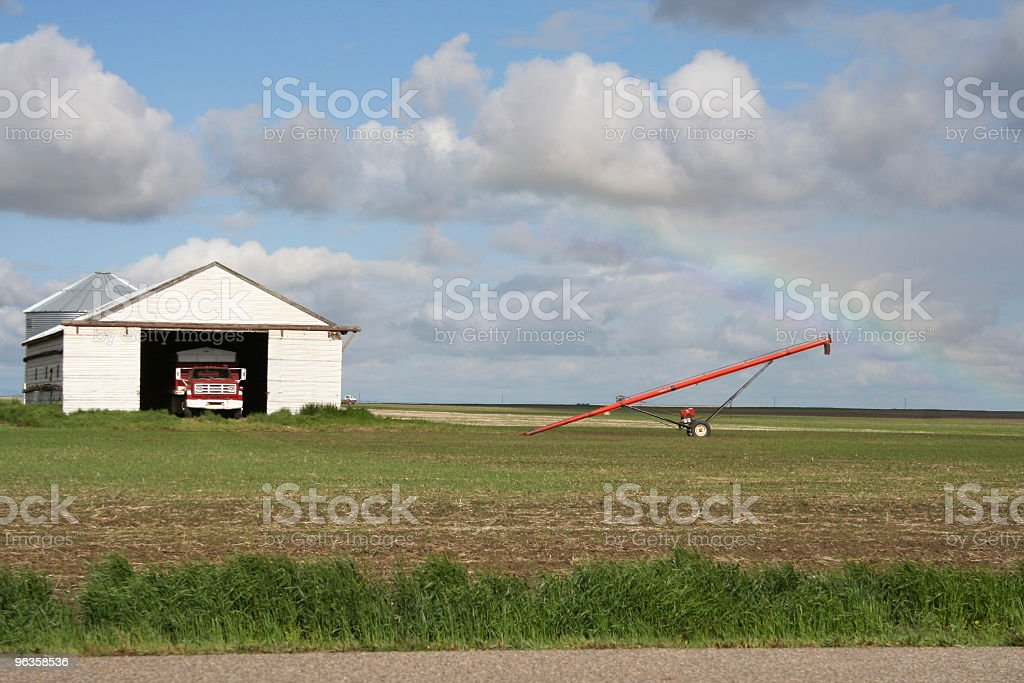 rainbow over auger, quonset and tandum truck in field royalty-free stock photo