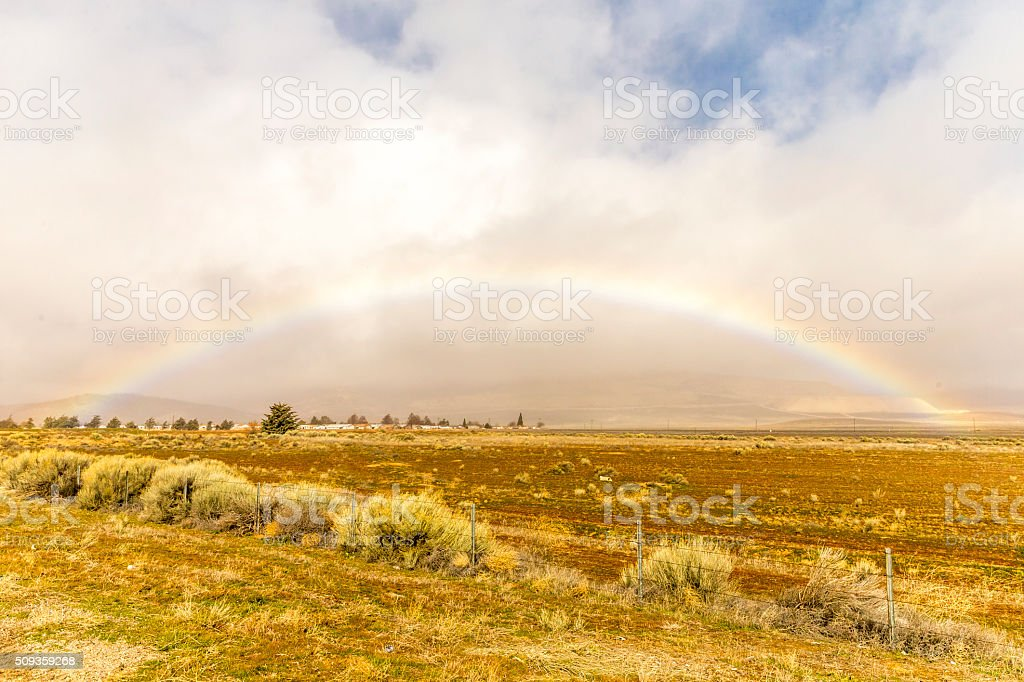 Rainbow over California field stock photo