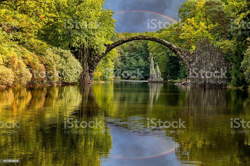 Rainbow over Devil's bridge in the park Kromlau, Germany stock photo