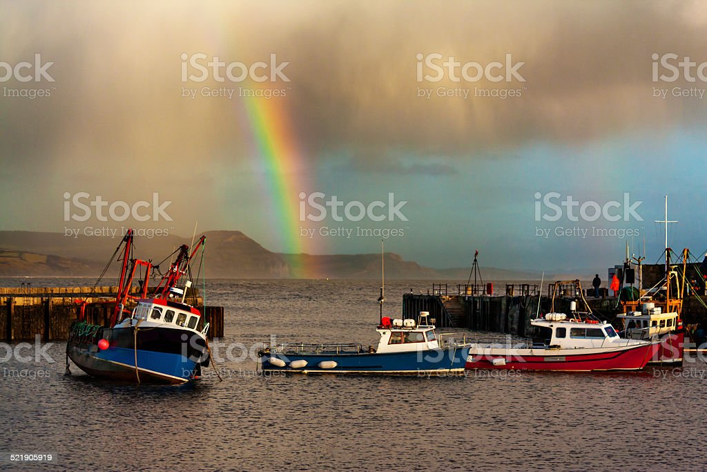 Rainbow over fishing boats at Lyme Regis stock photo