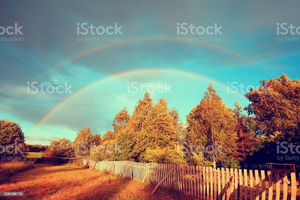 Rainbow over forest and field stock photo