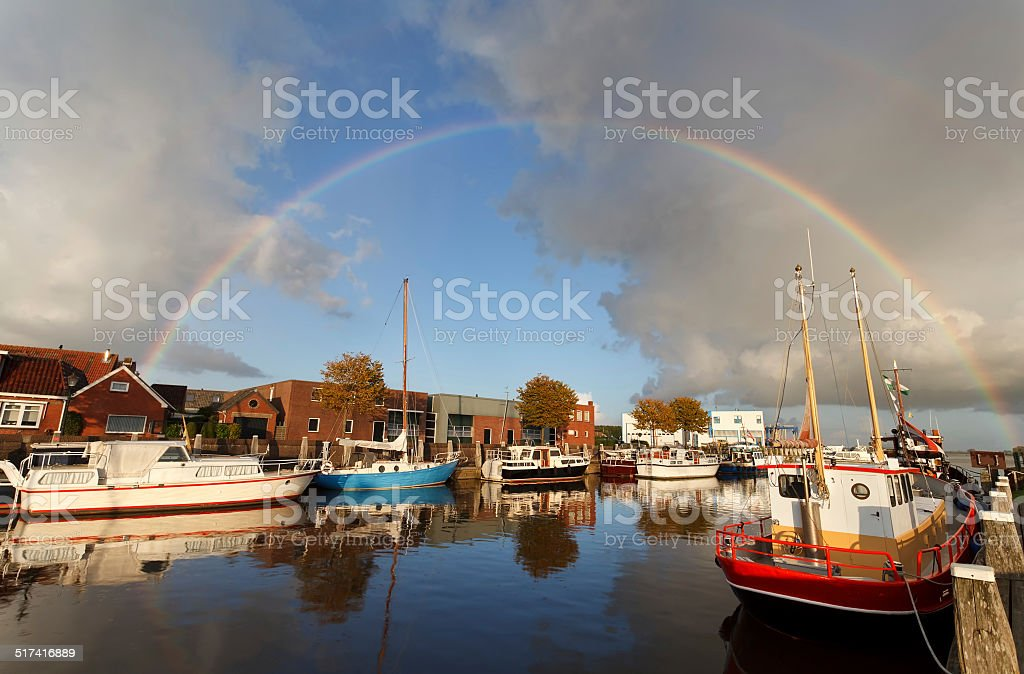 rainbow over harbor in Zoutkamp stock photo