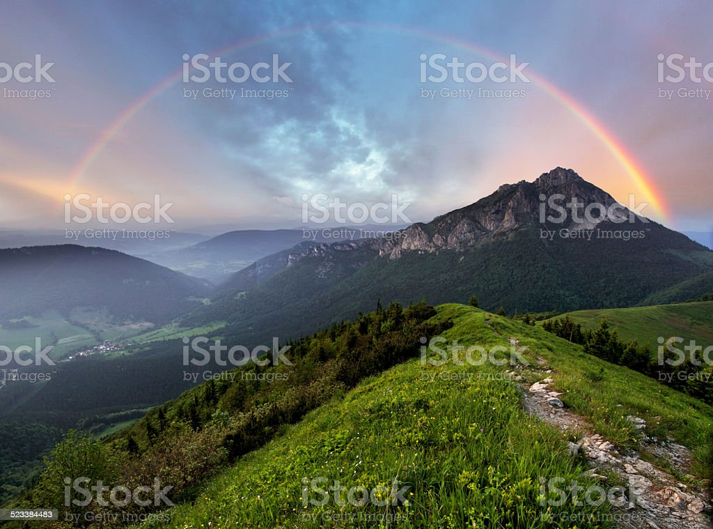 Rainbow over mountain peak stock photo