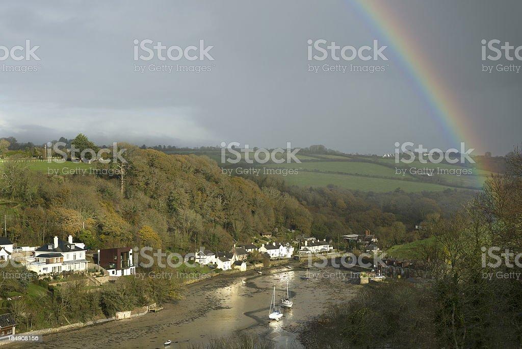 Rainbow over the village stock photo