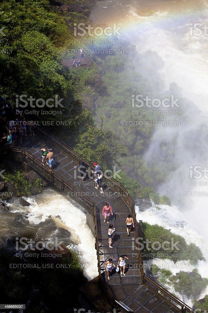 Rainbow over tourists on the walkways of Iguazu falls, Argentina royalty-free stock photo