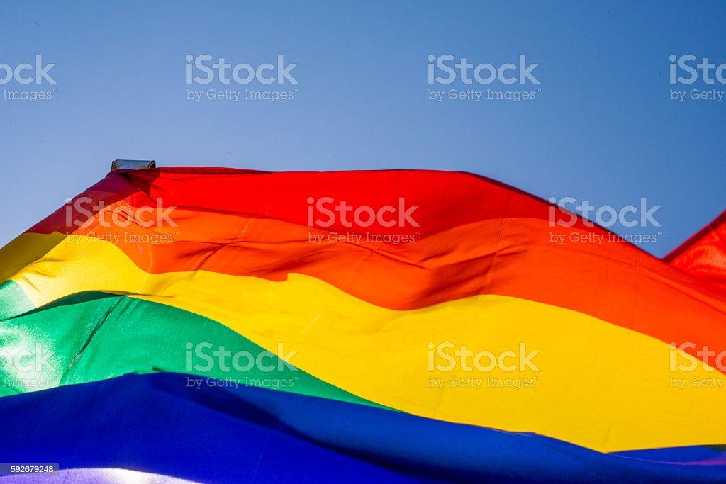 rainbow pride flag waving during pride parade stock photo