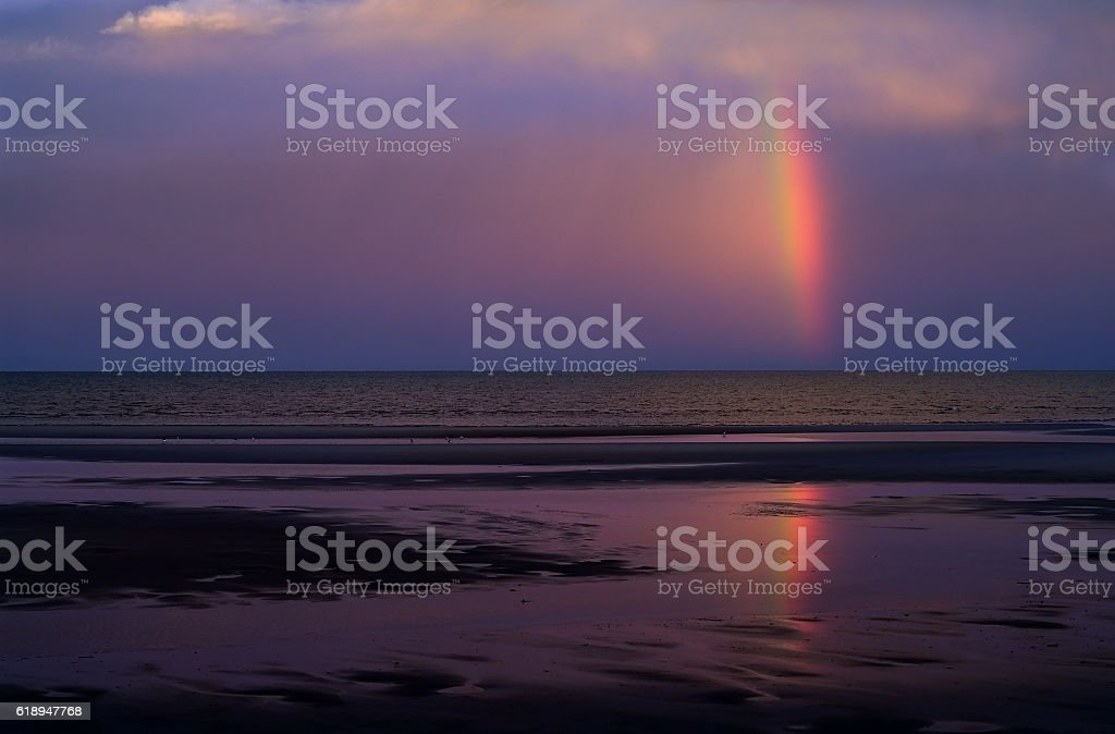 Rainbow reflected in tidal flats following early evening thunderstorm stock photo