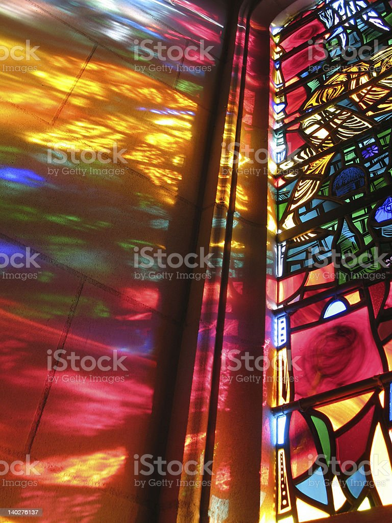 A rainbow spectrum reflection off of a stained glass window stock photo