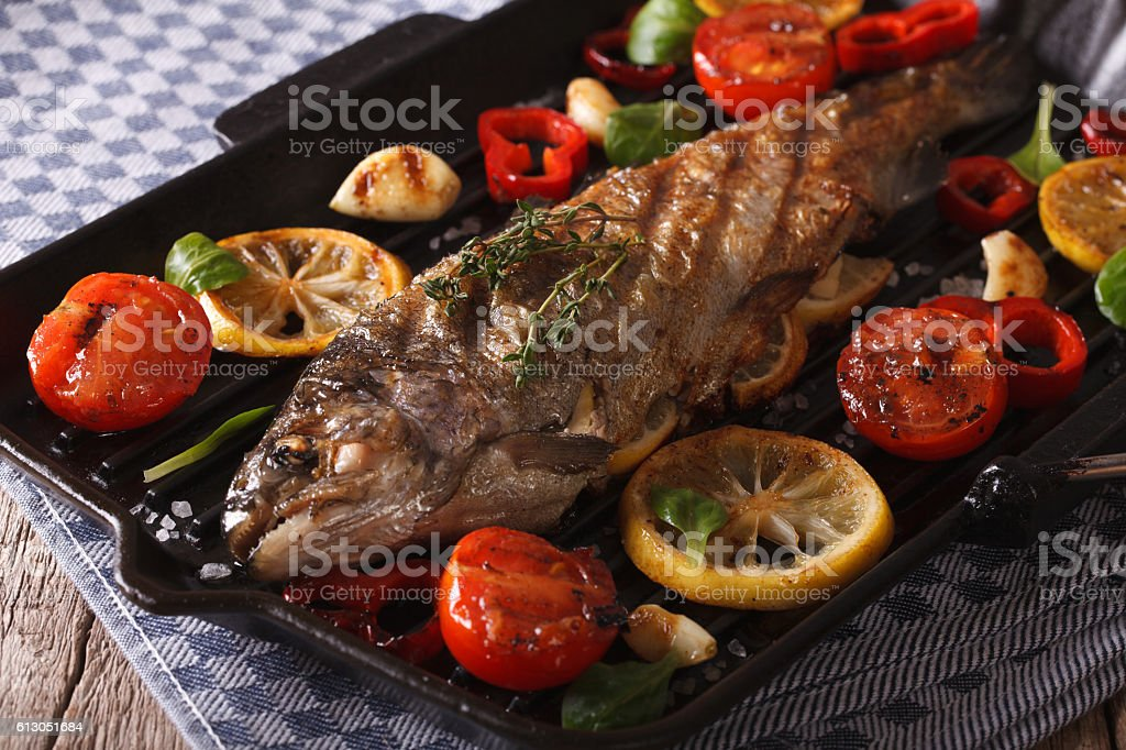 rainbow trout with vegetables on a grill pan close-up. horizontal stock photo