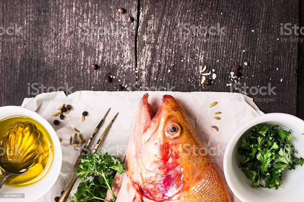 Rainbow trout,oil and spices on white paper stock photo