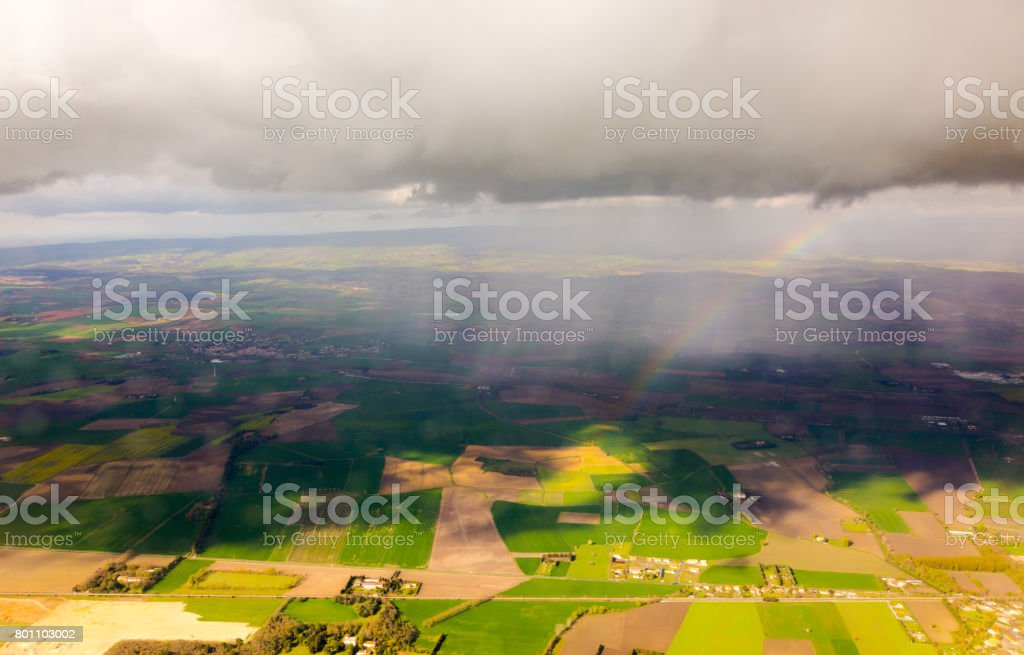 Rainbow under clouds over aerial view plots of fields stock photo