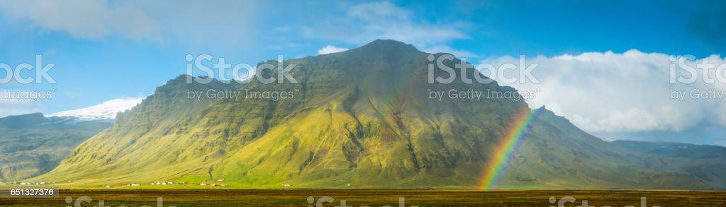 Rainbows and sunlight illuminating remote mountain farms panorama Iceland stock photo