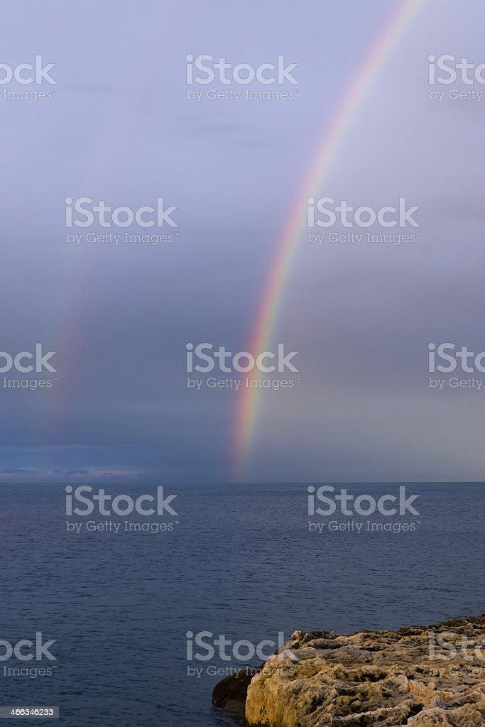Rainbows on water horizon. stock photo