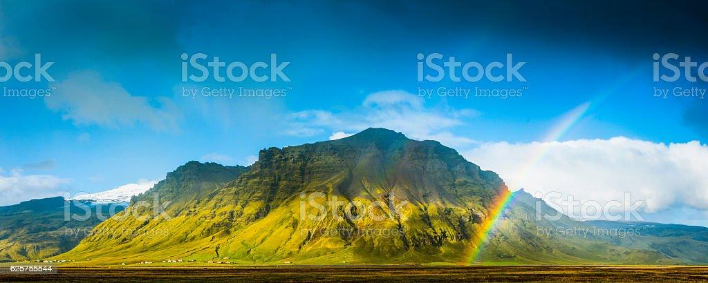 Rainbows over green mountain rural farmland pasture panorama Iceland stock photo