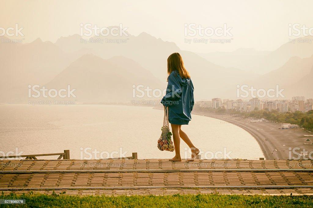 Raincoat girl looking at the sea stock photo