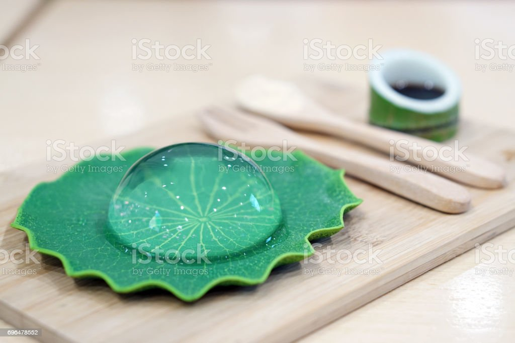 Raindrop Cake or Water Cake, also known as Mizo Suishyo Mochi on lily pad tray, Japanese Dessert Style. stock photo