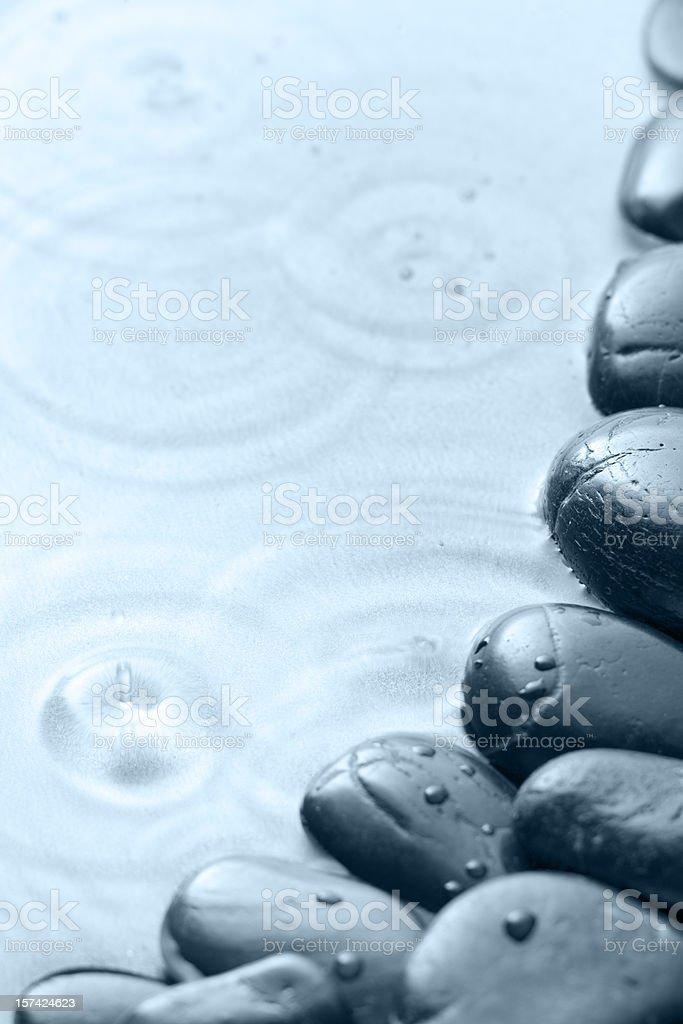 Raindrops falling on black pebbles royalty-free stock photo