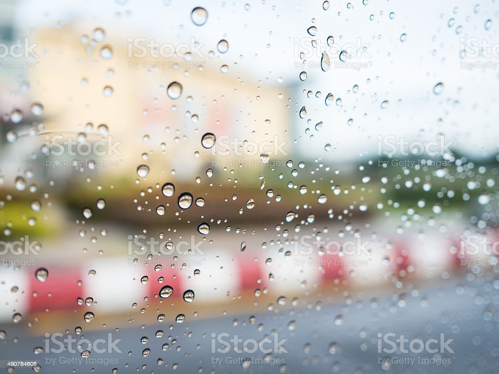 Raindrops on car glass with blurry footpath and building background. royalty-free stock photo
