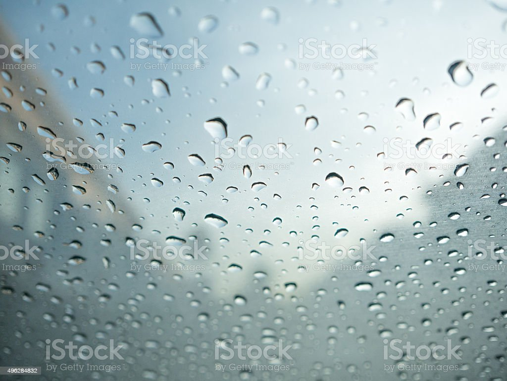 Raindrops on car's glass with blurry cloudy sky and village. royalty-free stock photo