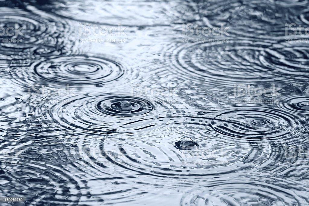 Raindrops on puddle stock photo