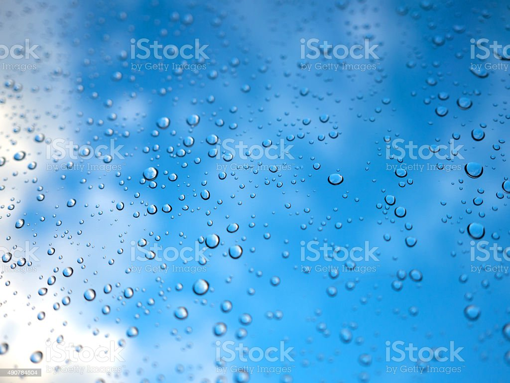 Raindrops on the glass with blurry blue sky. royalty-free stock photo