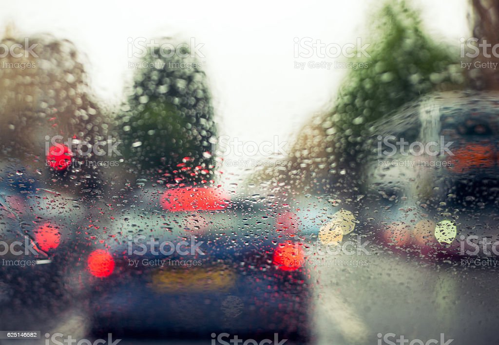 Raindrops on the windscreen with defocused traffic in the rain stock photo