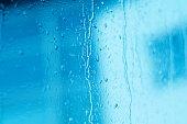 Raindrops on window glass, toned blue, tilt shift