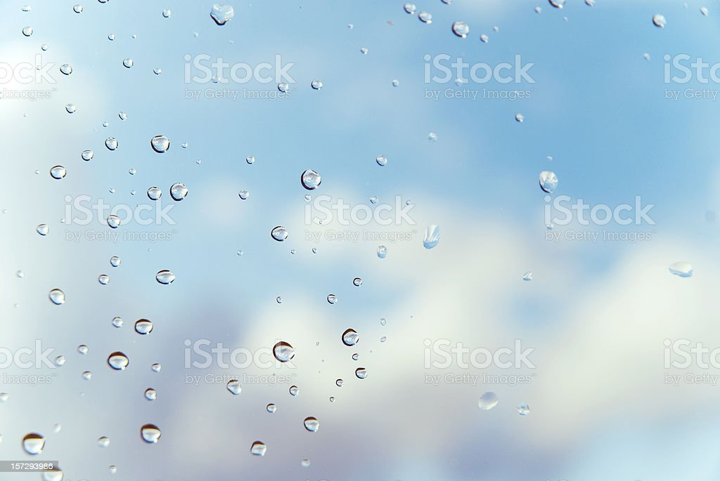 Raindrops on window with clouds and blue sky in background royalty-free stock photo