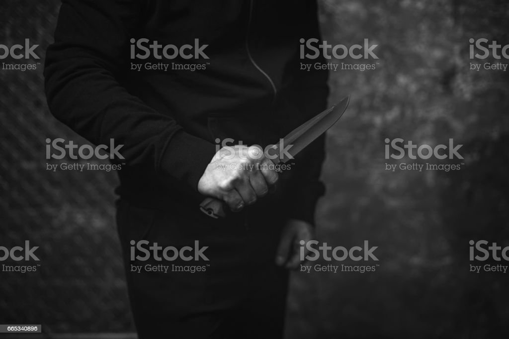 Raining hateful law breaker holding a dagger stock photo