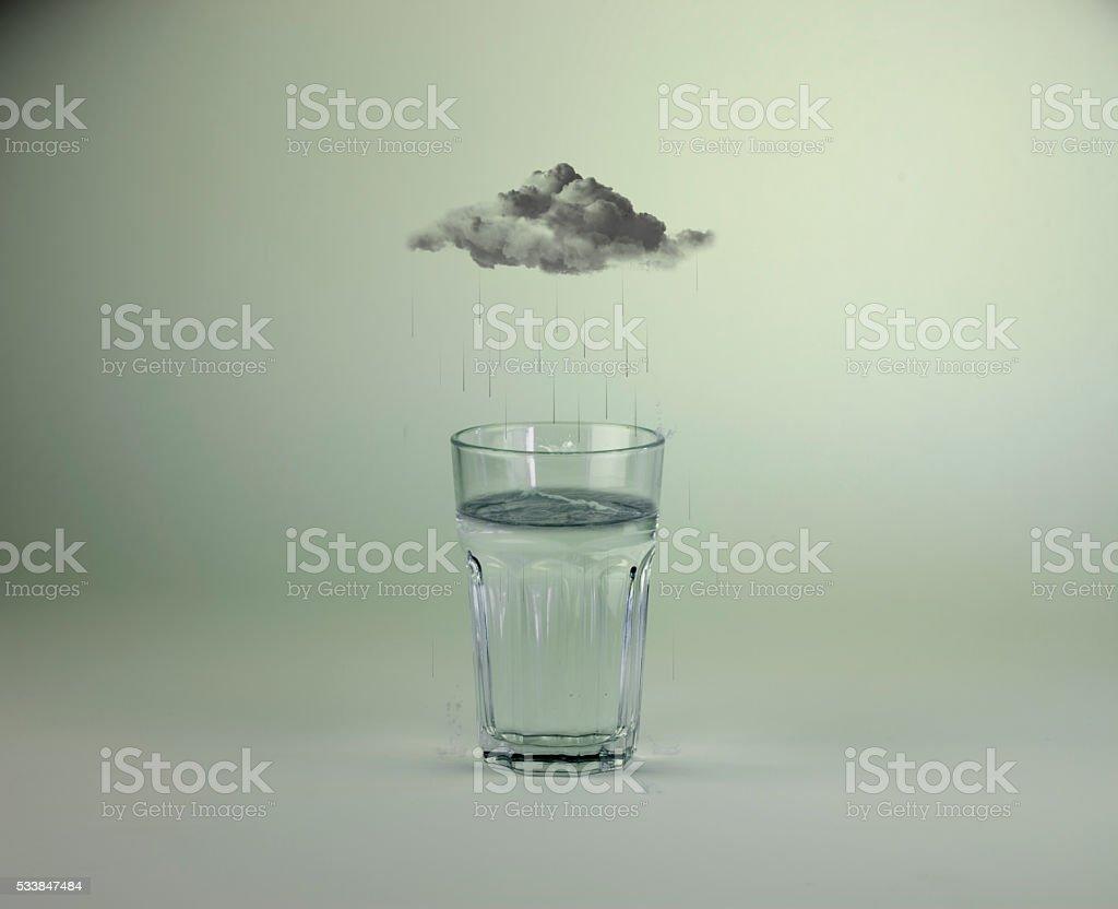 Raining into glass of water stock photo